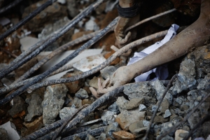 PADANG, INDONESIA - OCTOBER 03: Hands protrude from rubble as rescue efforts continue on October 3, 2009 in Padang, Indonesia. An earthquake of magnitude 7.6 struck at 5.16pm local time 85km under the sea north-west of Padang on September 30. According to reports officials have reported a death toll of 700 in the port city of Padang. However, that is expected to rise to over 1,000. (Photo by Daniel Berehulak/ Getty Images)